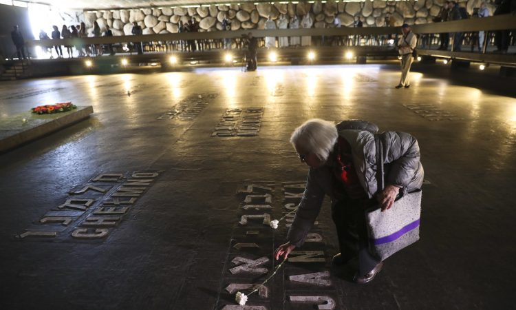A woman lays a flower at the Yad Vashem Holocaust memorial on Remembrance Day